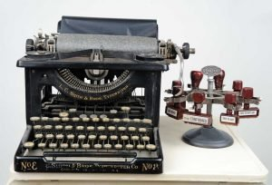 """Small sculpture by Ruth Lozner titled """"Ar t crtc is in,"""" Typewriter, typewriter stand, carbon paper, rubber stamps, 22"""" x 39"""" x 16"""""""