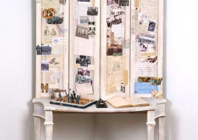 """Collage titled """"War, Peace, War, Peace, War, Peace… (the Cultivation of Soldiers),""""Collage, various found objects, including a WW11 Medic's Log, slide specimens, and Morse Code device, ephemera and photos, 42"""" x 75"""" x 15"""" created by Ruth Lozner"""
