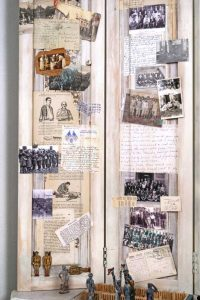 """Collage Detail 4 titled """"War, Peace, War, Peace, War, Peace… (the Cultivation of Soldiers),""""Collage, various found objects, including a WW11 Medic's Log, slide specimens, and Morse Code device, ephemera and photos, 42"""" x 75"""" x 15"""" created by Ruth Lozner"""